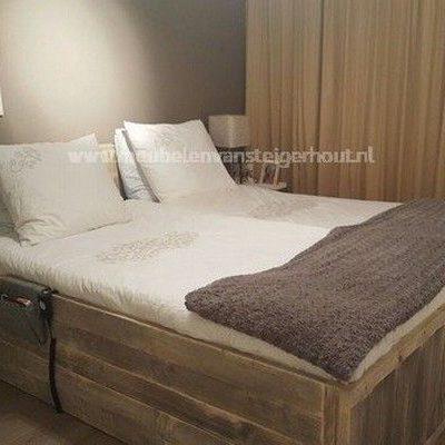 Steigerhouten bed met hoog hoofdboard dat dient als achterwand