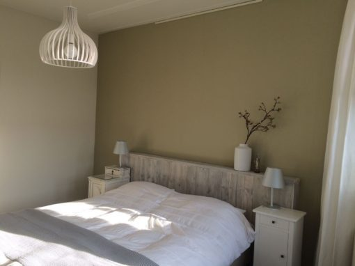 Steigerhouten wand achter het bed in whitewash