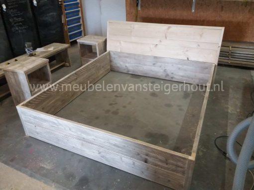 Bed van steigerhout met verhoogd hoofdeinde bekleed met leer